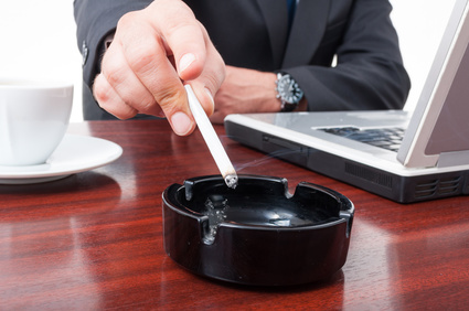 Close-up of ashtray with cigarette on office desk